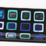 "Dichroic and irid glass squares on black platter. Item number 20: 17 1/2"" x 4 1/2"""
