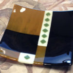 "Wood grained glass, black, green and ivory plate. Item number 32: 10"" by 10"""