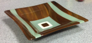 "Bowl comprised of wood tones blend with warm green and white: Item number 82: 11"" by 11"". Price: $45"