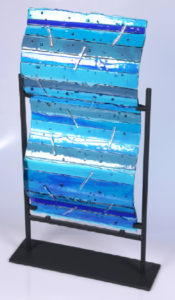 "Art glass piece that can be displayed on the wall or in a holder. Dimensional shades of blue transparent glass with dichroic bars. Item number 39: 10"" by 18"". Price: $300"