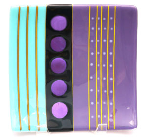 "Modern display plate with circles of purple dichroic glass showcasing bars of aqua, purple and yellow glass. Item number 52: 10"" by 10"". Price: $150"
