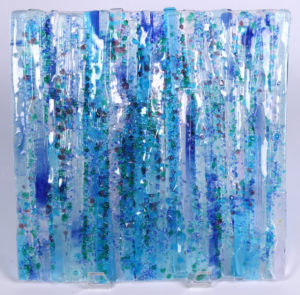 "A rain of shades of blue, green and clear strips of glass and colored glass dots make up this dimensional textured showcase piece! Item #145: 12"" by 12"". Price: $250"