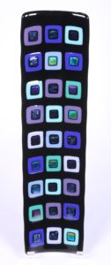 "Rainbow dichroic glass squares catch the light on this beautiful black platter with purples, blues and greens. Item number 151: 17 1/2"" x 4 1/2"". Cost: $125.00"