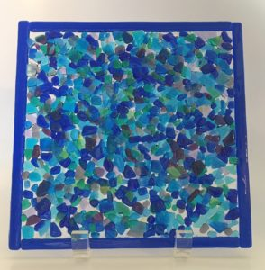 "Beautiful dimensional transparent display piece in blues, greens, and purples. Item number 189: 8"" square. Shown in vertical clear acrylic display stand. Cost: $45.00. Cost with stand: $50.00."