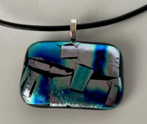"""Dichroic pendant with gorgeous blue, green and silver design. Item number N63: 1 1/2"""" x 1"""" inches. Price: $25"""